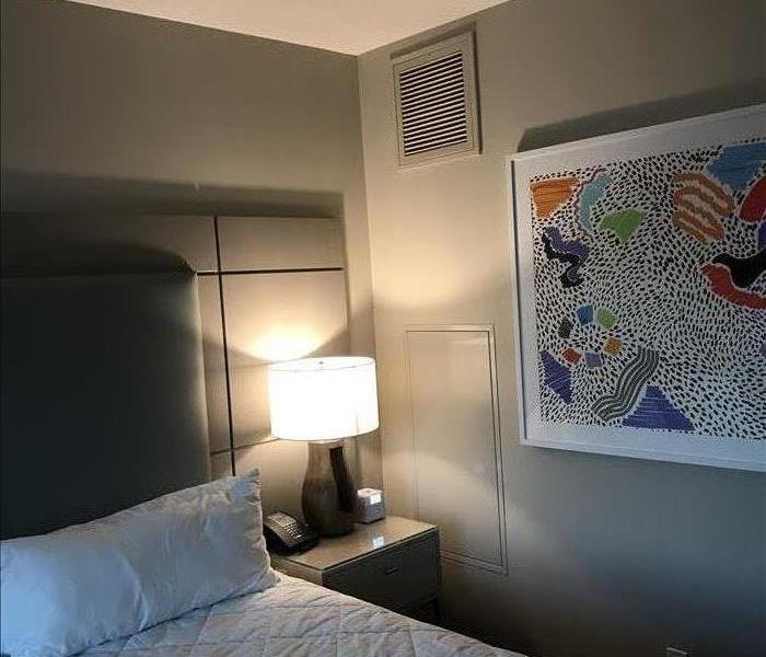 Hotel Bedroom after construction completed with walls completely redone and bed in the background made