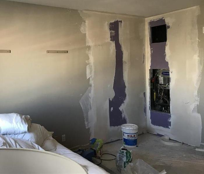Hotel Bedroom with drywall and mudding with a bed in the background