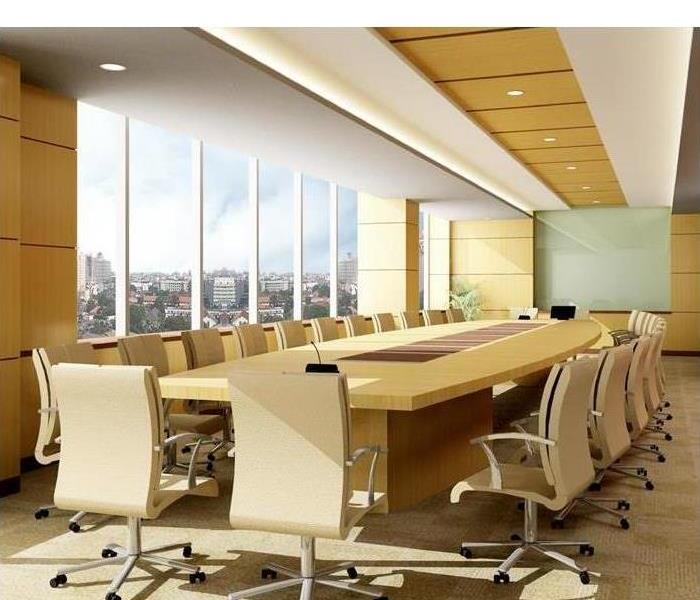 White conference table in an office with glass windows.